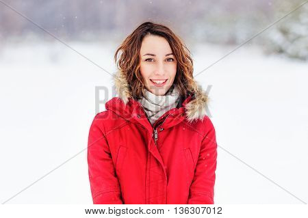 Girl in a red coat walks winter day
