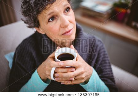 Close-up of thoughtful mature woman holding coffee cup at home
