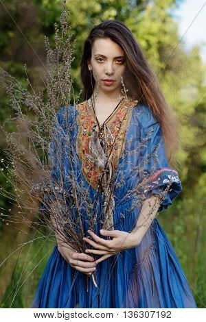 Young gipsy in blue dress at the forest