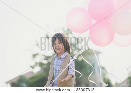 Cute Asian child with many balloons playing in the park under sunlight on summer day
