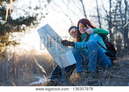 Young couple looking at map while sitting on grass.