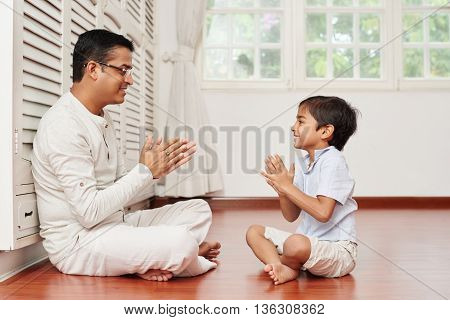 Indian man and his son sitting on the floor and playing together