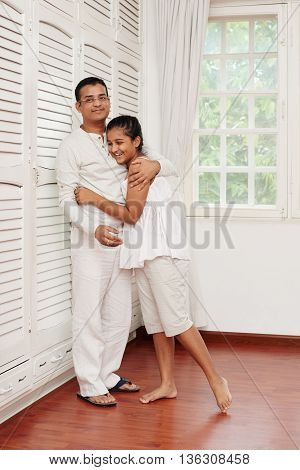 Indian smiling teenage girl hugging her father