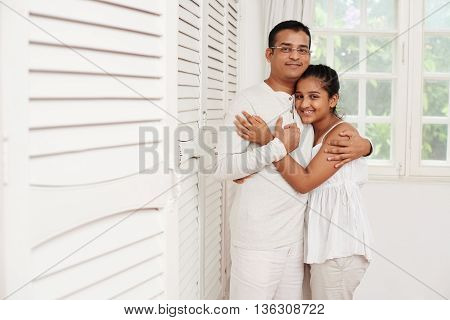 Indian father and daughter hugging and looking at camera