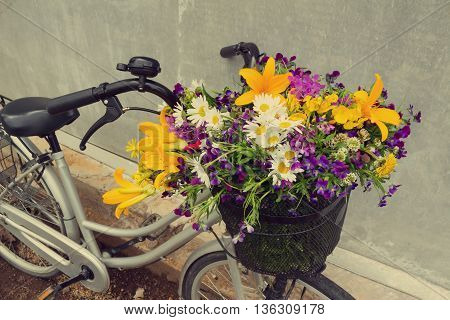 Bicycle with the basket full of beautiful field flowers lily violets chamomiles. Vintage toning