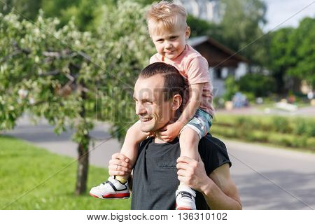 Son on the shoulders of his father in the park