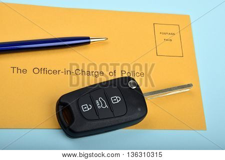 black car key and blue pen with a police correspondence envelope
