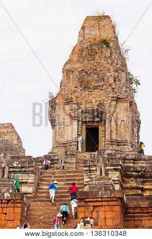SIEM REAP CAMBODIA - January 27 2011. Tourists climb up the Banteay Srei - 10th century Hindu temple dedicated to Shiva. Angkor area of Cambodia.