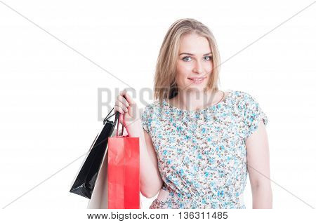 Joyful trendy shopper female wearing summer dress and carrying gift bags isolated on white background