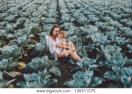 Mom and daughter having fun on the field with cabbage