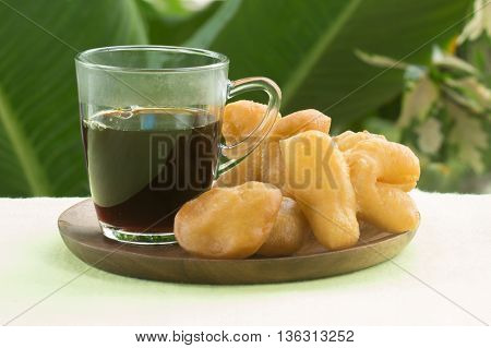 deep fried dough stick on the wooden tray with black coffee