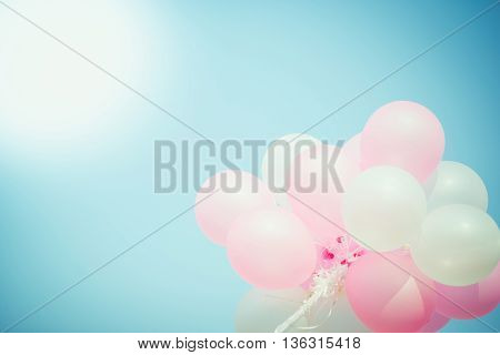 Pink and white balloon on blue sky with copy space vintage filter