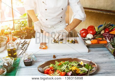 Hands with knife cut olives. Vegetable salad on tray. Green olives and tiger shrimp. Restaurant chef has serious skills.