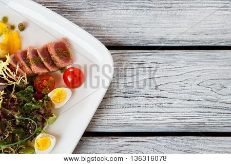 Plate with salad. Salad with tomatoes and meat. Quail eggs and fried tuna. Organic meal served at bistro.