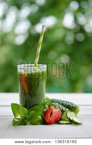 Green smoothie with strawberry as healthy summer drink