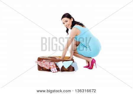 Travel concept. Portrait of stylish beautiful young woman wearing dress and high heels shoes. Isolated on white background. Woman packing vintage suitcase full of clothes, smiling and looking at camera