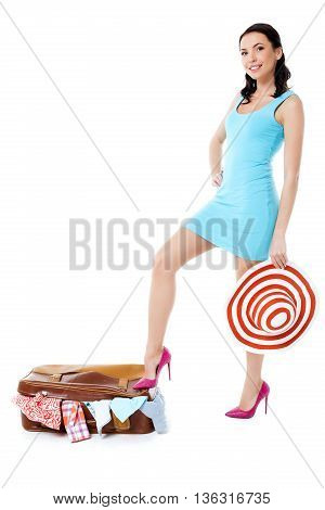 Travel concept. Portrait of stylish beautiful young woman wearing dress, hat and high heels shoes. Isolated on white background. Woman with suitcase full of clothes smiling and looking at camera