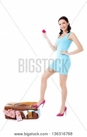 Travel concept. Portrait of stylish beautiful young woman wearing high heels shoes. Isolated on white background. Woman with suitcase full of clothes smiling, holding credit card and looking at camera
