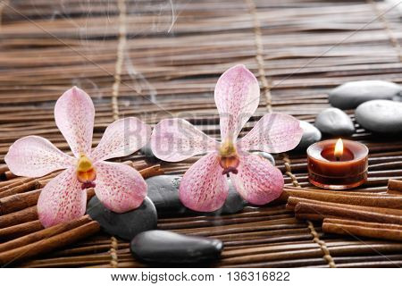 Two orchid, gray stones cinanam  on mat