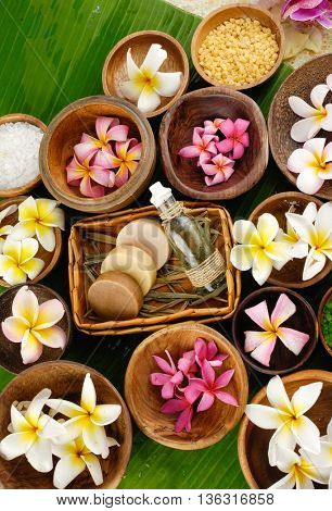 many colorful frangipani and salt in bowl ,soap, oil on palm leaf