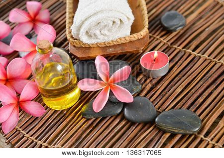 Spa setting with candle ,towel, oil with mat texture