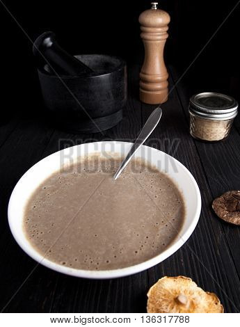 Creamy vegan mushroom soup with champignon and shiitake in white bowl. Dark photo with black wood background. Mortar, pepper mill and jar with mushroom powder on back. Dry shiitake on front.