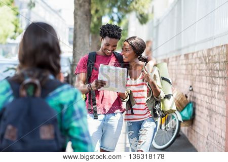Happy young couple looking at map and talking