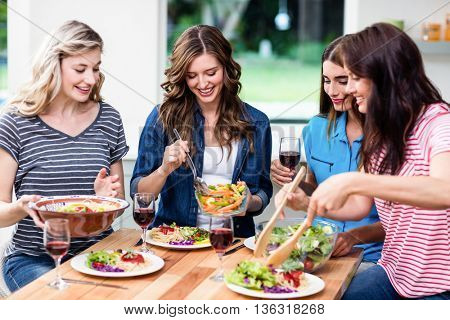 Smiling friends having food at table