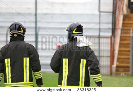 Two Helmeted Firemen For The Security Service In The Stadium