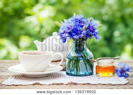 Tea cup teapot honey jar and summer bouquet of blue cornflowers on table outdoors. Summer still life.
