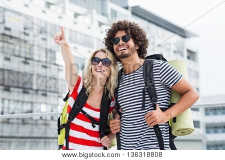 Young couple in sunglasses standing on terrace with rucksack