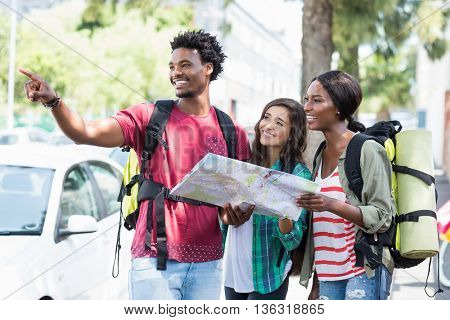 Friends holding map and pointing outdoors
