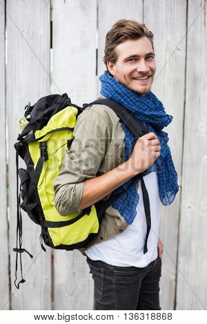 Happy young man carrying backpack outdoors