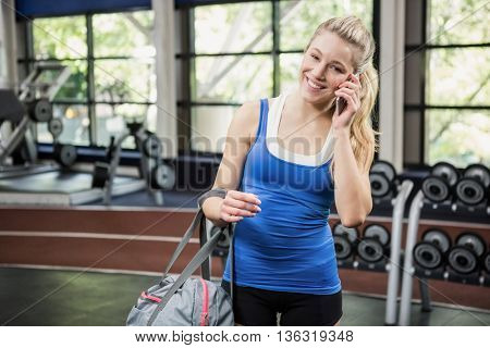 Woman with gym bag talking on the phone in weights room at gym