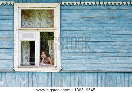 Sad bored little girl looking out the country house window leaning her face on her hand. Outside view
