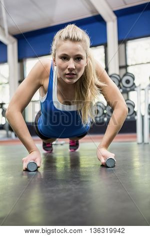 Determined woman doing push ups at gym