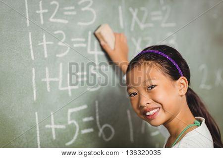 Girl using a sponge for blackboard at school