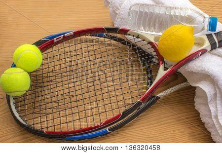 Concept - sport. Tennis rackets and balls are next to a bottle of water and lemon.