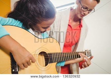 Girl learning how to play the guitar with the help of a teacher