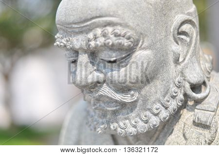 Close up face of chinese hermit stone statue
