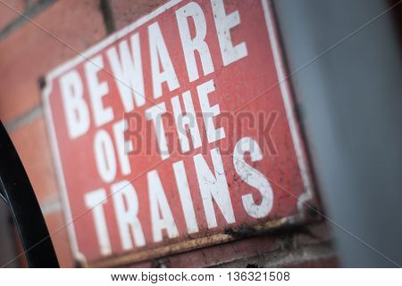 Old vintage red retro distressed railway enamel metal sign with text, beware of the trains
