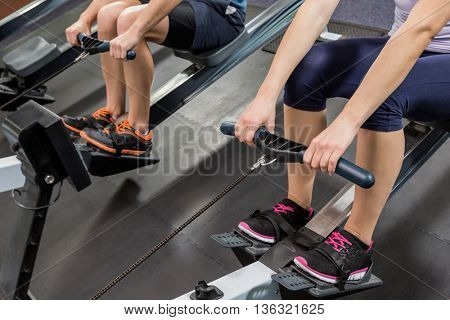 Mid section of people exercising on rowing machine at gym