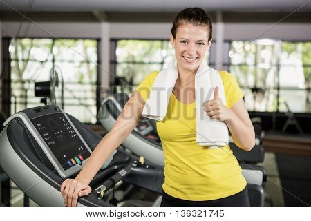 Portrait of happy woman showing her thumbs up at gym
