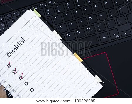 Handwriting Checklist on blank notebook with laptop keyboard