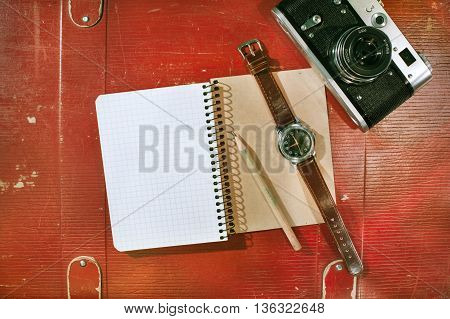 Travel concept - men set with suitcase, empty notepad, pencil, wrist watch,  vintage film camera, on brown leather background. Top view
