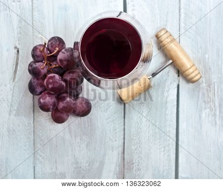 A photo of a glass of red wine with a bunch of grapes and an old wooden corkscrew shot from above on a light blue wooden background texture with copyspace
