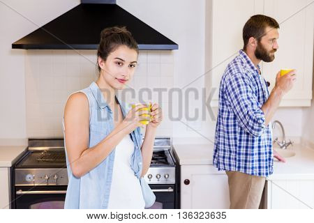 Young couple having cup of coffee in kitchen at home