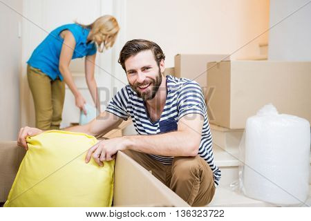 Young couple assisting each other while unpacking cartons in new house