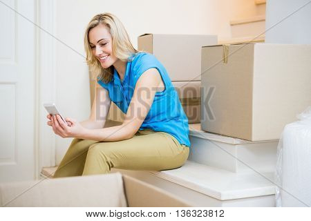 Smiling young woman looking at mobile phone in new house