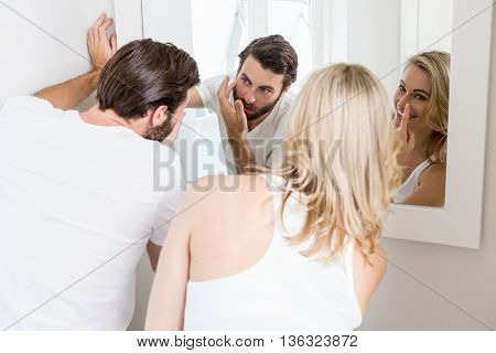 Young couple applying cream on the face in the bathroom